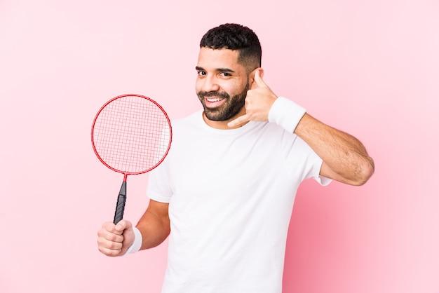 Junger arabischer mann, der badminton spielt