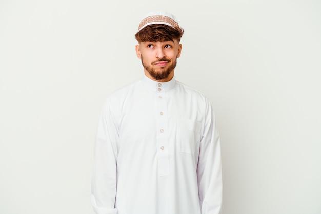 Junger arabischer mann, der das typische arabische kostüm trägt, das auf weißem hintergrund isoliert verwirrt ist, fühlt sich zweifelhaft und unsicher.