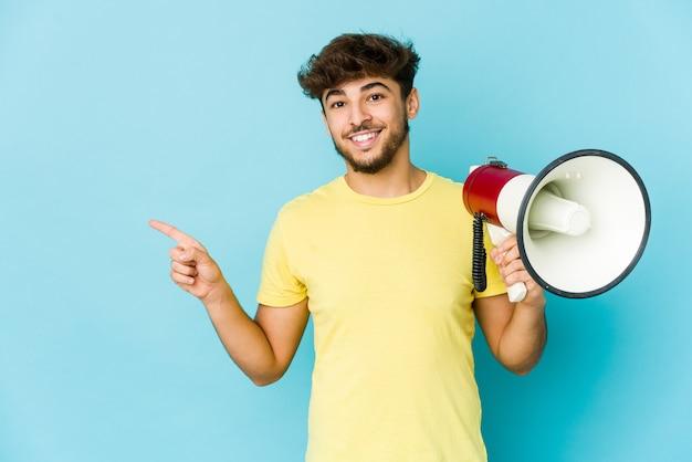 Junger arabischer mann, der ein megaphon hält, das lächelt und zur seite zeigt und etwas an der leeren stelle zeigt.