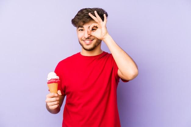 Junger arabischer mann, der eine aufgeregte eiscreme hält, die ok geste auf auge hält.