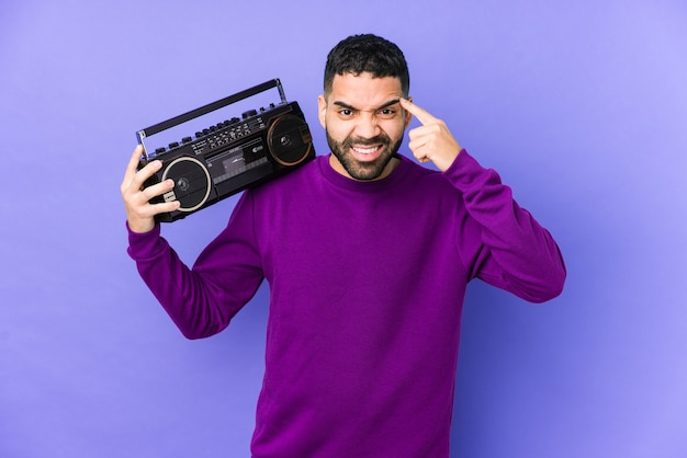 Junger arabischer mann, der eine radio-kassette isoliert hält junger arabischer mann, der musik hört, die eine enttäuschungsgeste mit zeigefinger zeigt.