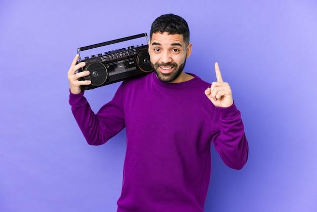 Junger arabischer mann, der eine radiokassette hält