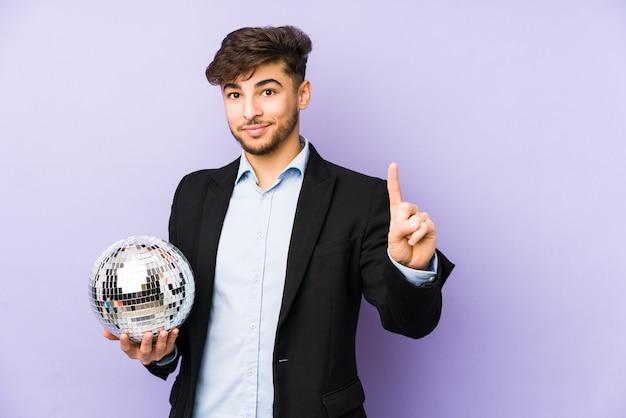 Junger arabischer mann, der einen isolierten partyball hält, der nummer eins mit finger zeigt.