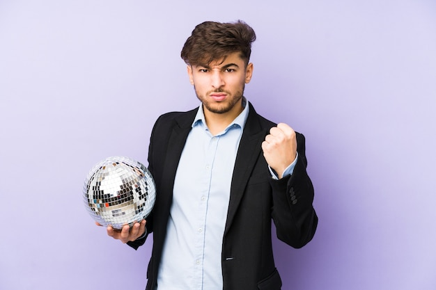 Junger arabischer mann, der einen isolierten partyball hält, zeigt faust, aggressiven gesichtsausdruck.