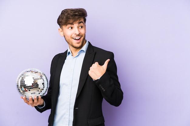 Junger arabischer mann, der einen partyball hält, isolierte punkte mit daumenfinger weg, lachend und sorglos.