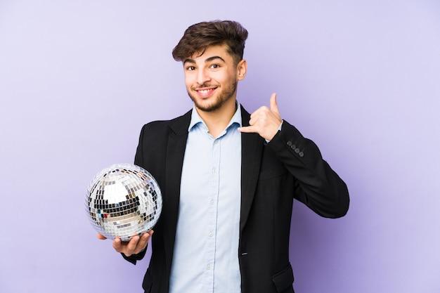 Junger arabischer mann, der einen partyball lokalisiert hält, der eine handy-anrufgeste mit den fingern zeigt.