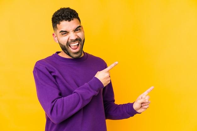 Junger arabischer mann der gemischten rasse, der mit zeigefingern auf einen kopierraum zeigt und aufregung und verlangen ausdrückt.
