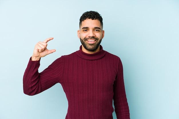 Junger arabischer mann der gemischten rasse isoliert, etwas wenig mit zeigefingern haltend, lächelnd und zuversichtlich.