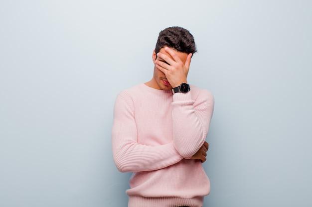 Junger arabischer mann, der gestresst, beschämt oder verärgert mit kopfschmerzen schaut und gesicht mit hand gegen graue wand bedeckt
