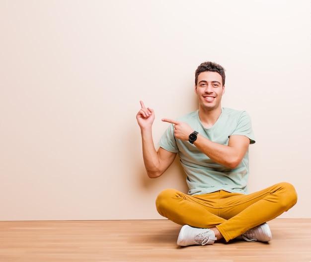 Junger arabischer mann, der glücklich lächelt und zur seite und nach oben zeigt, wobei beide hände objekt im kopienraum zeigen, der auf dem boden sitzt