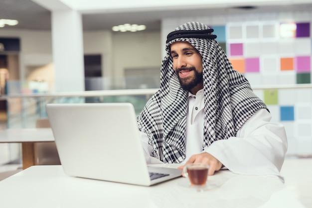 Junger arabischer mann, der handy im modernen mall verwendet.