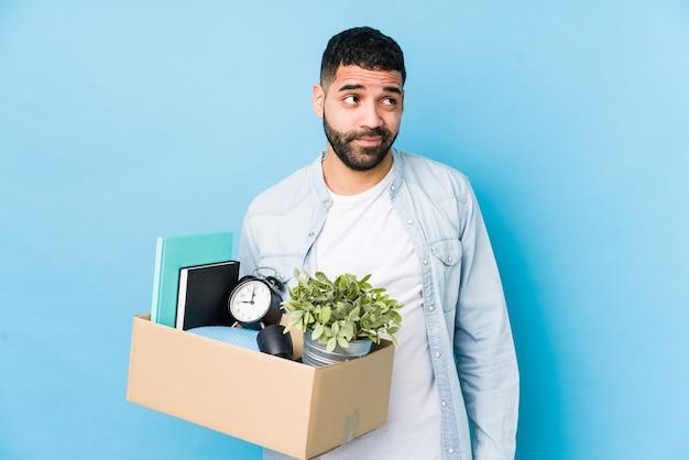 Junger arabischer mann, der in ein neues zuhause zieht, isoliert davon, ziele und zwecke zu erreichen