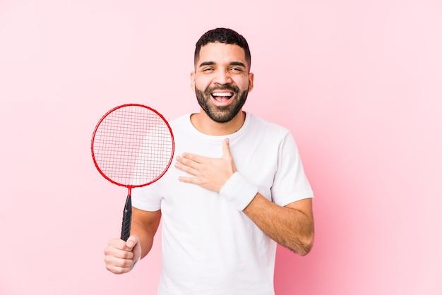 Junger arabischer mann, der isoliert badminton spielt, lacht laut und hält hand auf brust.