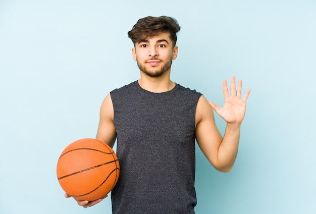 Junger arabischer mann, der korb spielt, isoliert lächelnd fröhlich zeigt nummer fünf mit den fingern.