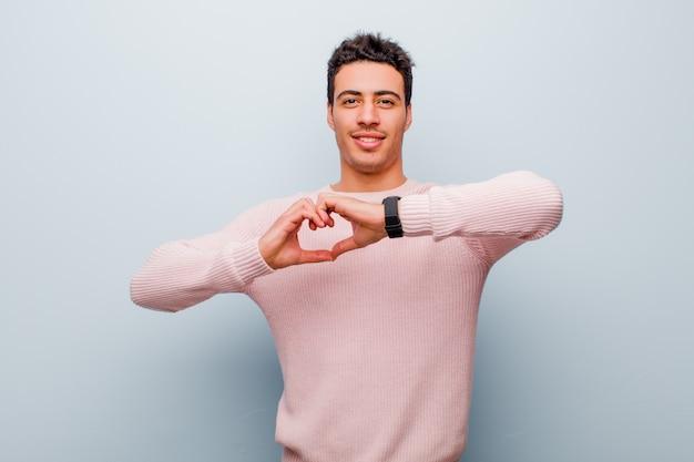 Junger arabischer mann, der lächelt und sich glücklich, niedlich, romantisch und verliebt fühlt und herzform mit beiden händen gegen graue wand bildet