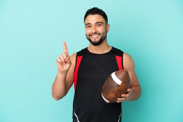 Junger arabischer mann, der rugby spielt, isoliert auf blauem hintergrund, der einen finger im zeichen des besten zeigt und hebt