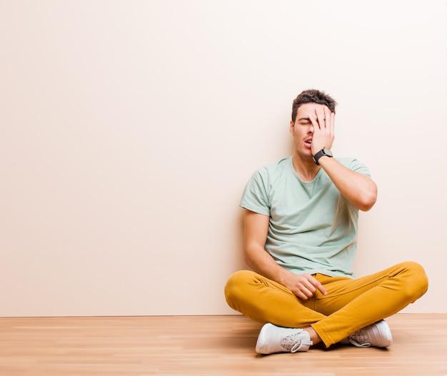 Junger arabischer mann, der schläfrig, gelangweilt und gähnend aussieht, mit kopfschmerzen und einer hand, die das halbe gesicht bedeckt, das auf dem boden sitzt