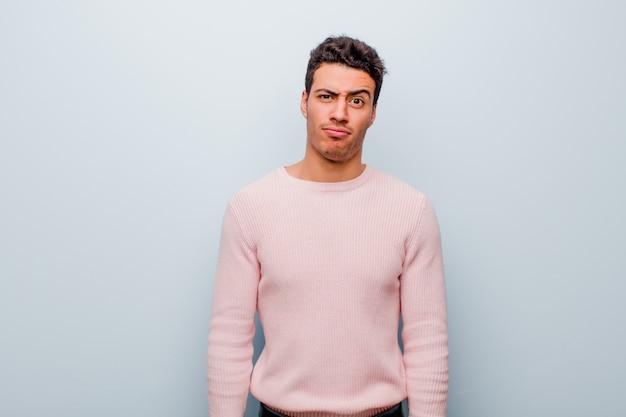 Junger arabischer mann, der sich verwirrt und zweifelhaft fühlt, sich wundert oder versucht, eine graue wand zu wählen oder eine entscheidung zu treffen