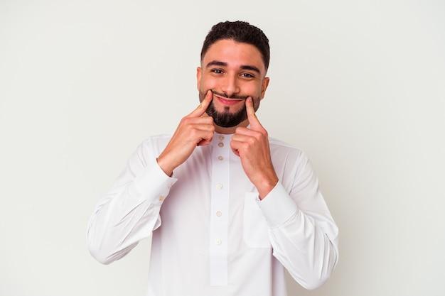Junger arabischer mann, der typisch arabische kleidung trägt, isoliert auf weißem hintergrund, der zwischen zwei optionen zweifelt.