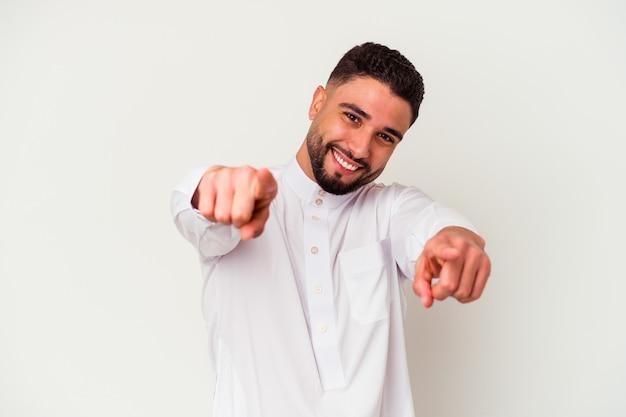 Junger arabischer mann, der typische arabische kleidung lokalisiert auf weißem hintergrund freudiges lächeln trägt, zeigt nach vorne.