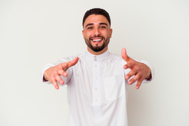 Junger arabischer mann, der typische arabische kleidung trägt, die auf weißem hintergrund isoliert wird, fühlt sich zuversichtlich, der kamera eine umarmung zu geben.