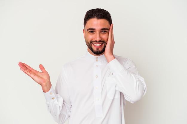 Junger arabischer mann, der typische arabische kleidung trägt, die auf weißem hintergrund isoliert wird, hält kopienraum auf einer handfläche, hand über wange halten