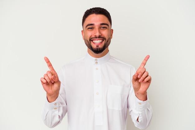 Junger arabischer mann, der typische arabische kleidung trägt, die auf weißem hintergrund isoliert wird, zeigt mit beiden vorderfingern an, die eine leerstelle zeigen.