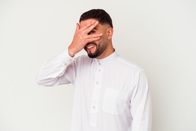 Junger arabischer mann, der typische arabische kleidung trägt, die auf weißem hintergrund lokalisiert wird, blinzelt an der kamera durch finger, verlegenes bedeckendes gesicht.