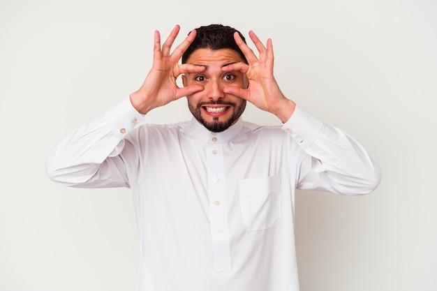 Junger arabischer mann, der typische arabische kleidung trägt, die auf weißem hintergrund lokalisiert wird, hält augen offen, um eine erfolgschance zu finden.