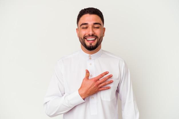 Junger arabischer mann, der typische arabische kleidung trägt, die auf weißem hintergrund lokalisiert wird, lacht laut und hält hand auf brust.