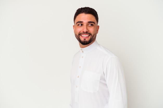 Junger arabischer mann, der typische arabische kleidung trägt, die auf weißem hintergrund lokalisiert wird, schaut beiseite lächelnd, fröhlich und angenehm.
