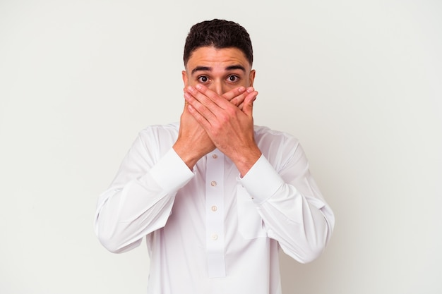 Junger arabischer mann, der typische arabische kleidung trägt, die auf weißem hintergrund lokalisiert wird, schockierte, mund mit händen bedeckend.