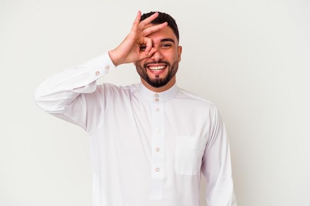 Junger arabischer mann, der typische arabische kleidung trägt, lokalisiert auf weißem hintergrund aufgeregt, ok geste auf auge haltend.