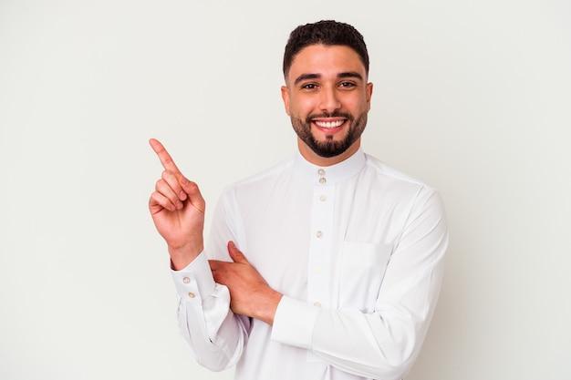 Junger arabischer mann, der typische arabische kleidung trägt, lokalisiert auf weißem hintergrund, der fröhlich mit zeigefinger weg zeigt.