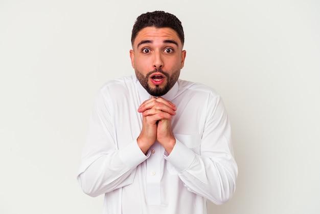 Junger arabischer mann, der typische arabische kleidung trägt, lokalisiert auf weißem hintergrund, der für glück betet, erstaunt und mund öffnet, der nach vorne schaut.
