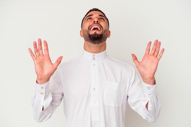 Junger arabischer mann, der typische arabische kleidung trägt, lokalisiert auf weißem hintergrund, der zum himmel schreit und aufschaut, frustriert.