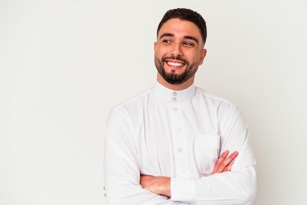 Junger arabischer mann, der typische arabische kleidung trägt, lokalisiert auf weißem hintergrund, der zuversichtlich mit verschränkten armen lächelt.