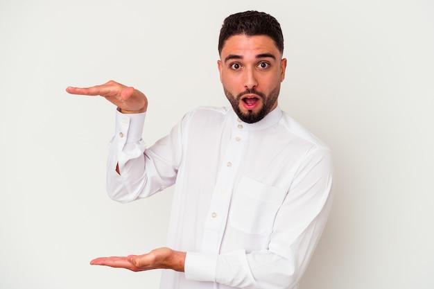 Junger arabischer mann, der typische arabische kleidung trägt, lokalisiert auf weißem hintergrund schockiert und erstaunt, einen kopierraum zwischen händen haltend.