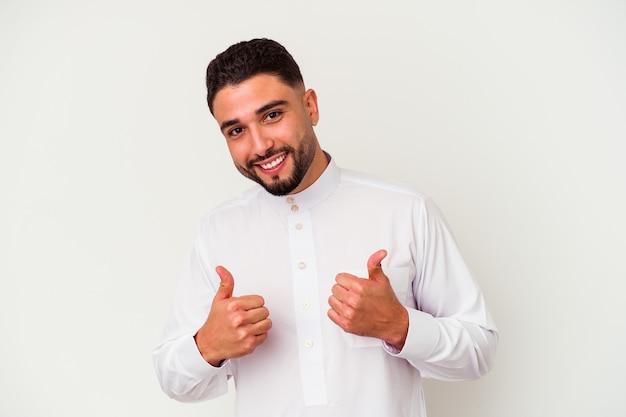 Junger arabischer mann, der typische arabische kleidung trägt, lokalisiert auf weißer wand, die beide daumen anhebt, lächelnd und zuversichtlich.