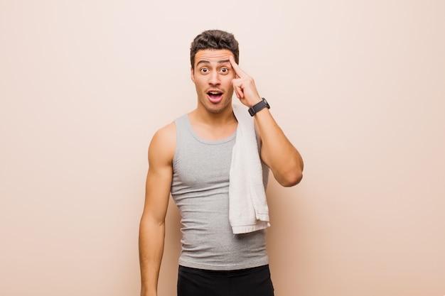 Junger arabischer mann, der überrascht, mit offenem mund, schockiert aussieht und einen neuen gedanken, eine neue idee oder ein neues konzept verwirklicht. sportkonzept