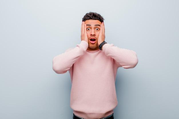 Junger arabischer mann, der unangenehm geschockt, verängstigt oder besorgt aussieht, mund weit offen und beide ohren mit händen gegen graue wand bedeckend