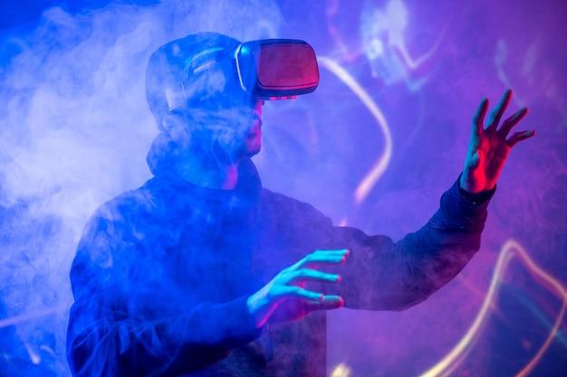 Junger arabischer mann, der virtual-reality-gerät verwendet, das hände im geräucherten vr-raum gestikuliert