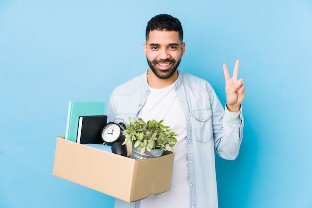 Junger arabischer mann, der zu einem neuen haus bewegt, isoliert, nummer zwei mit den fingern zeigend.