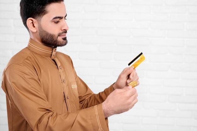 Junger arabischer mann hält bitcoin und goldene kreditkarte