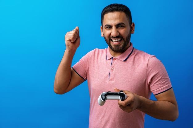 Junger arabischer mann im rosa t-shirt, der videospiele vor blauem hintergrund spielt