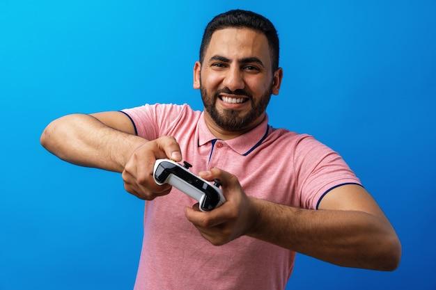 Junger arabischer mann in rosa t-shirt, der videospiele vor blauem hintergrund spielt Premium Fotos