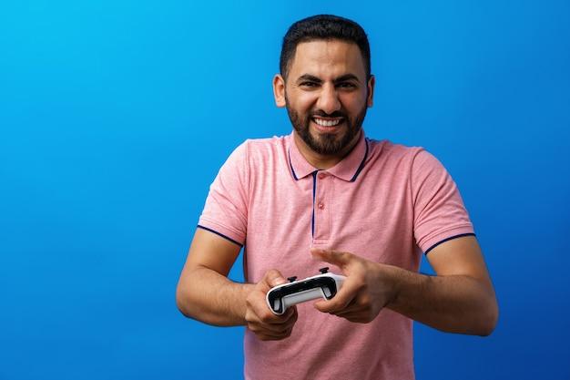 Junger arabischer mann in rosa t-shirt, der videospiele vor blauem hintergrund spielt
