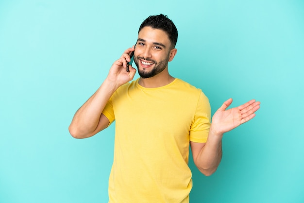 Junger arabischer mann isoliert auf blauem hintergrund, der ein gespräch mit dem handy mit jemandem führt