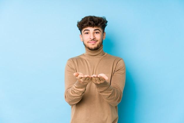 Junger arabischer mann isoliert, der etwas mit palmen hält und anbietet