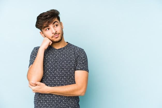Junger arabischer mann lokalisiert auf einer blauen wand, die sich traurig und nachdenklich fühlt und kopierraum betrachtet.